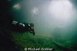 A diver in side-mount gear returns to the warm sunlit ent... by Michael Grebler 